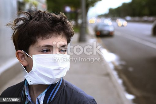 istock teenager boy in protection mask on the highway city 852229954