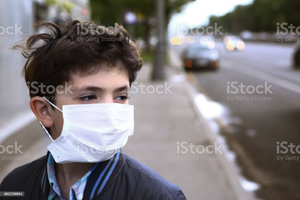 teenager boy in protection mask on the highway city stock photo