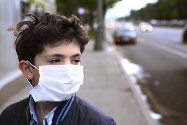 teenager boy in protection mask on the highway city - infectious disease stock pictures, royalty-free photos & images
