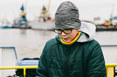 istock Teenager boy in winter hat, coat and glasses looking down seriously while standing next to waterfront in the harbor. 1208574217