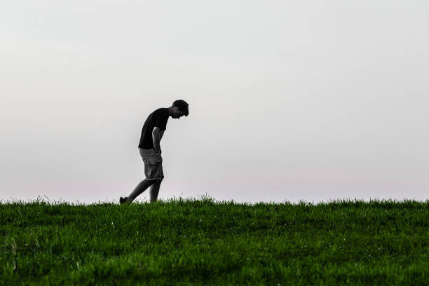 Teenager boy lonely and sad Teenage boy dejected, walking alone along a grassy meadow. bad posture stock pictures, royalty-free photos & images