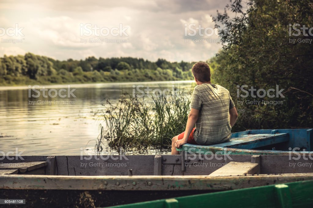 Teenager boy lonely contemplation countryside scenery on river boat during countryside summer holidays stock photo