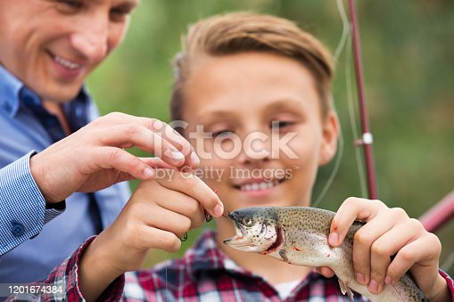 Glad teenager boy holding and looking at a fish on hook