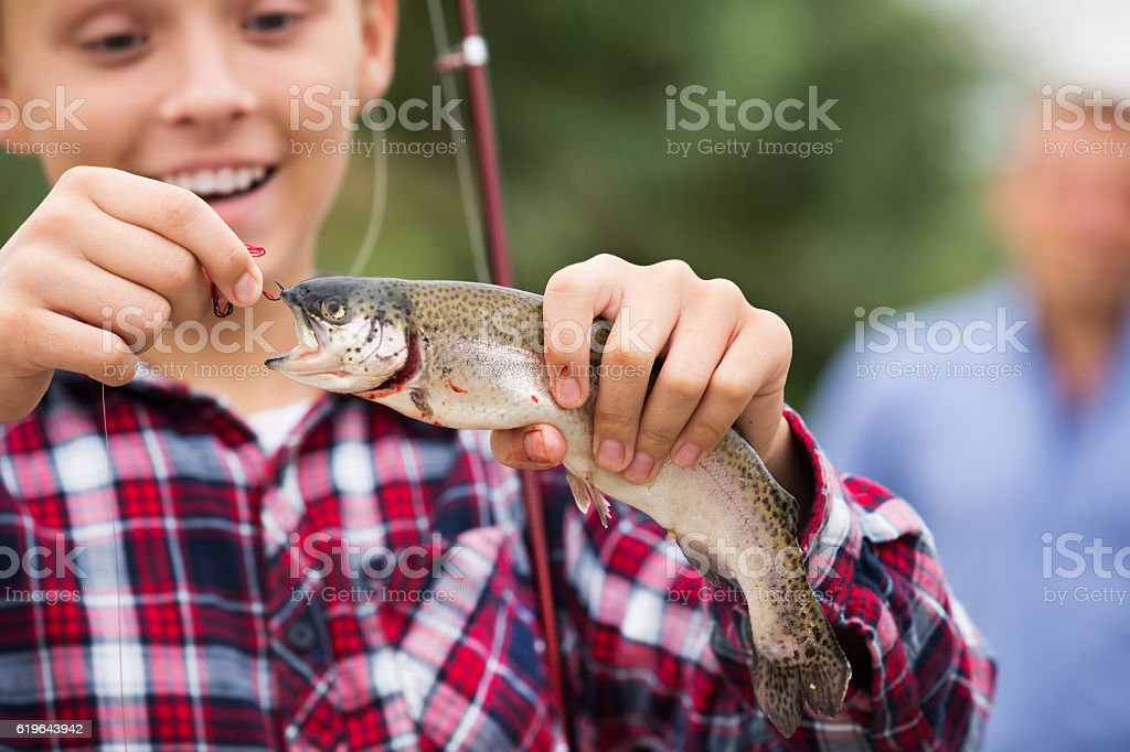 Teenager boy looking at fish on hook stock photo