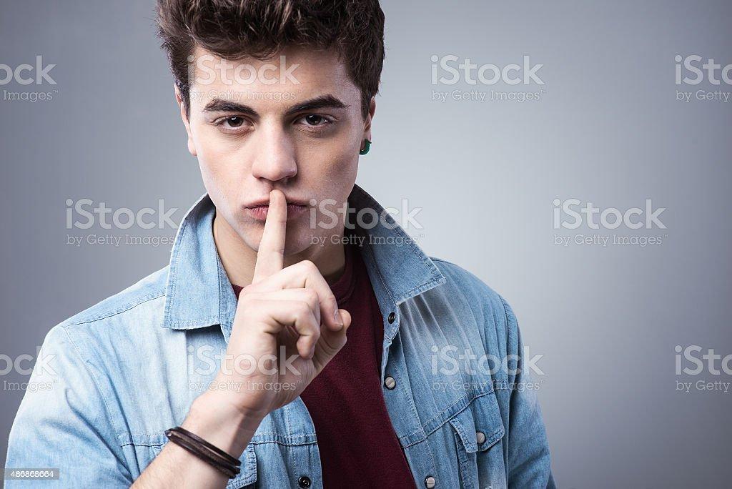 Teenager boy making silence gesture stock photo