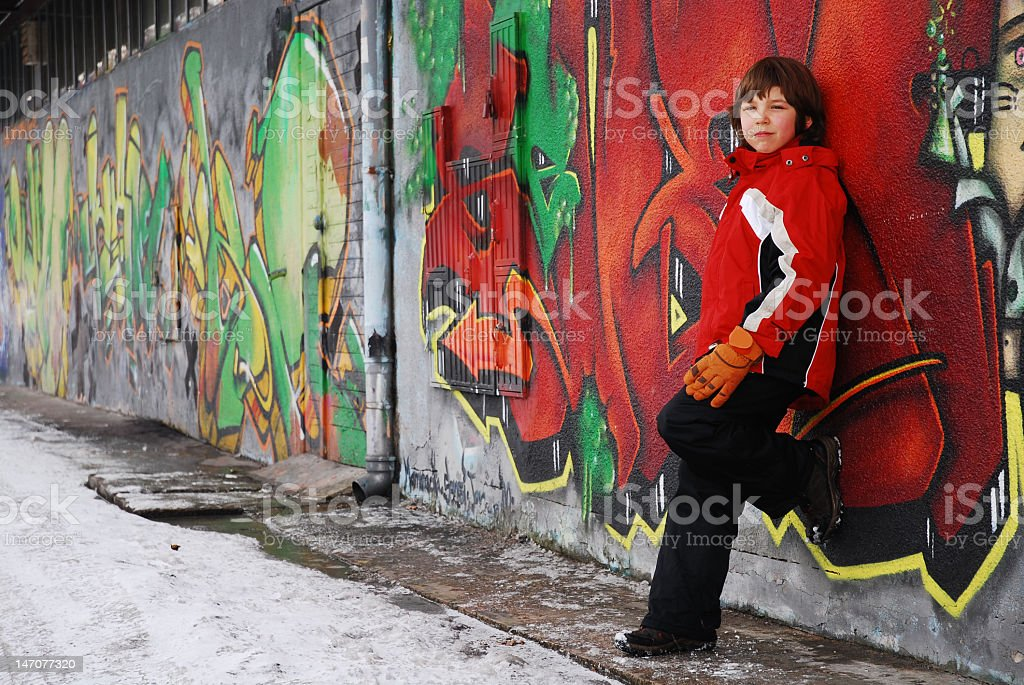 Teenager boy on the street against a graffiti wall royalty-free stock photo