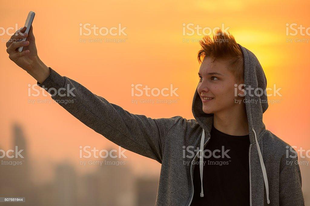 Teenager boy outdoors taking selfie stock photo