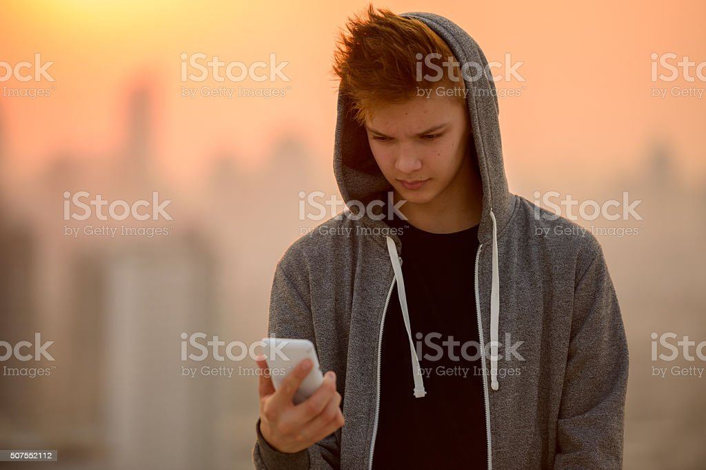 Teenager boy outdoors using mobile phone stock photo