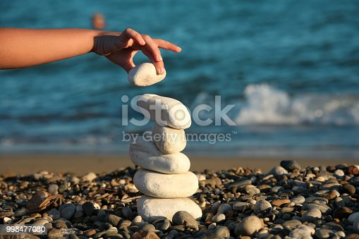 Close up teenager boy playing with stones on summer beach vacation