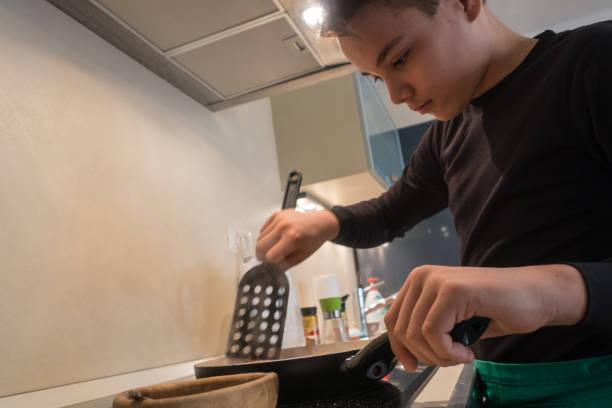Teenager Boy Hühnchen-Curry in der heimischen Küche vorbereiten – Foto