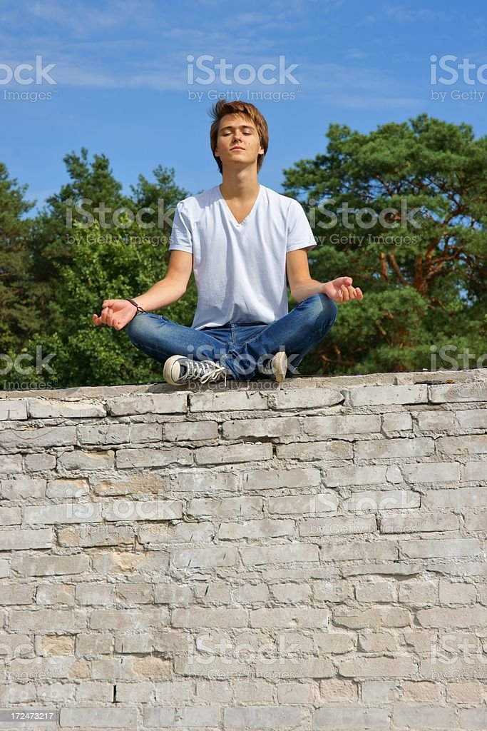 Teenager, boy sitting on a wall and meditates stock photo