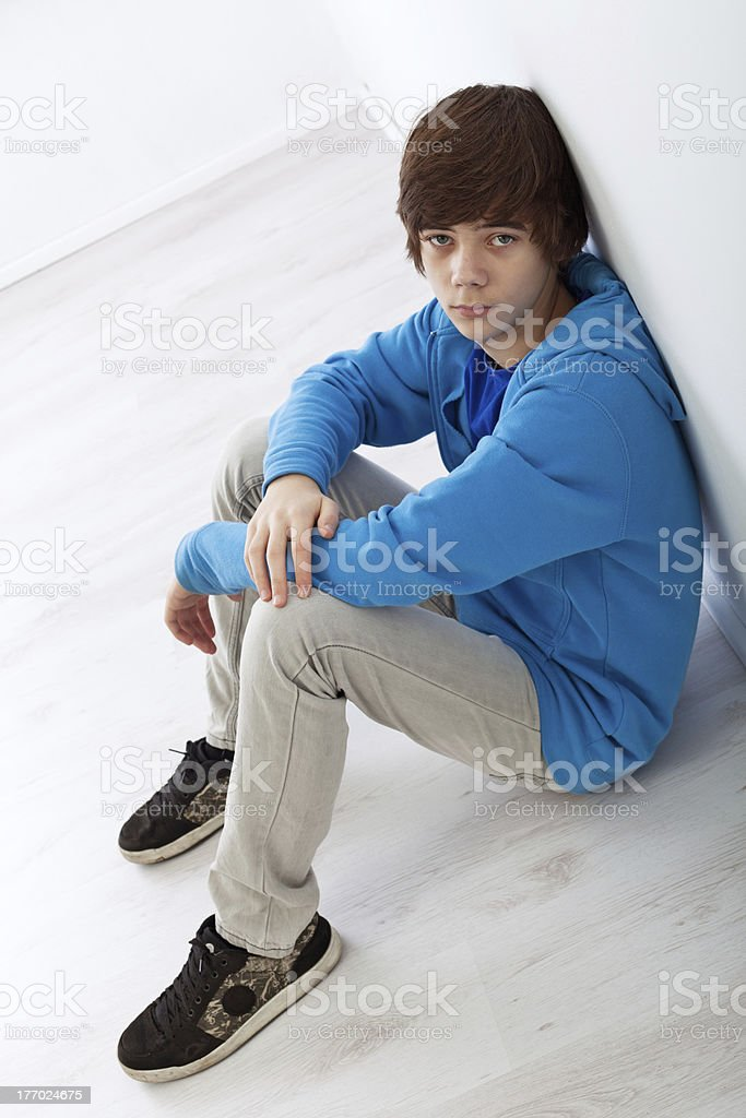 Teenager boy sitting on the floor royalty-free stock photo