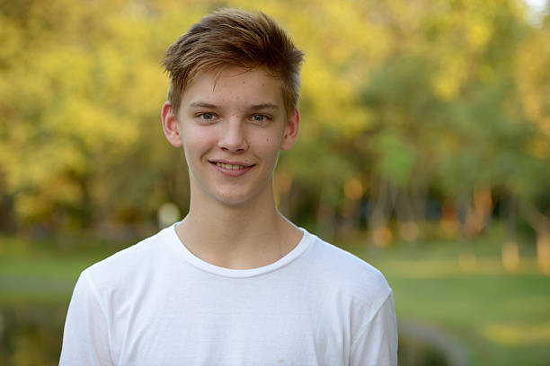 Teenager boy smiling outdoors in park stock photo