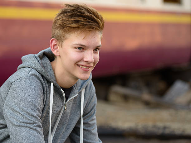 Teenager boy smiling outdoors stock photo