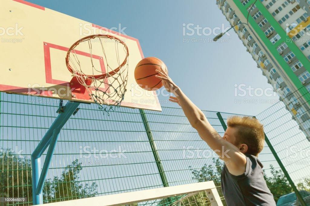 Teenager boy street basketball player on the city basketball court