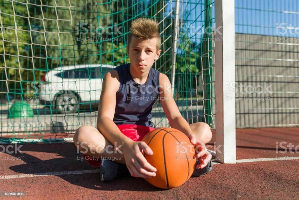 Teenager boy street basketball player on the city basketball court.