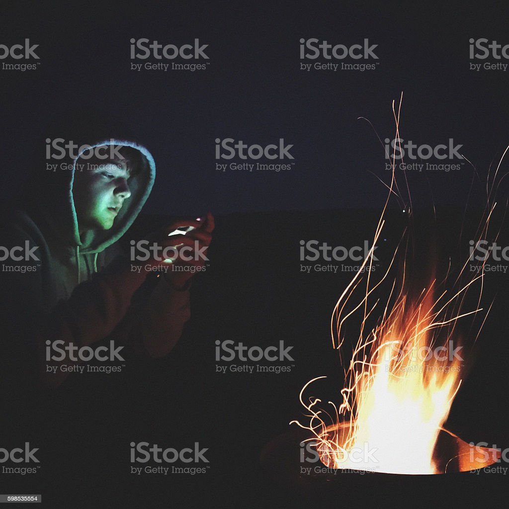 Teenager boy using smartphone by the campfire stock photo
