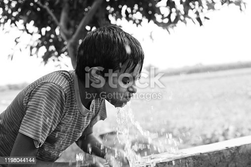 Teenager boy washing face outdoor in nature.
