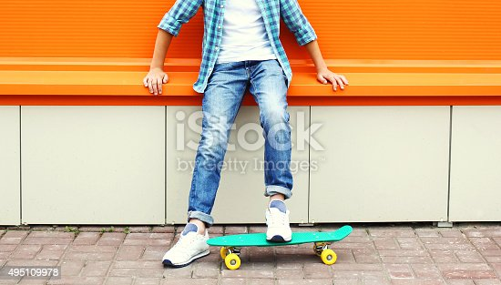 istock teenager boy wearing a checkered shirt and jeans on skateboard 495109978