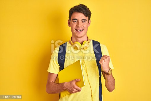 1175468850istockphoto Teenager boy wearing headphones and backpack reading a book over isolated background screaming proud and celebrating victory and success very excited, cheering emotion 1187194293