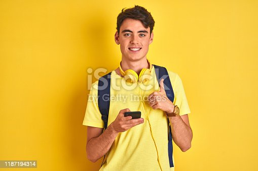 istock Teenager boy wearing headphones and using smartphone over isolated background happy with big smile doing ok sign, thumb up with fingers, excellent sign 1187194314