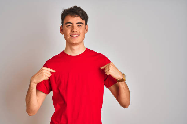 Teenager boy wearing red t-shirt over white isolated background looking confident with smile on face, pointing oneself with fingers proud and happy. Teenager boy wearing red t-shirt over white isolated background looking confident with smile on face, pointing oneself with fingers proud and happy. red shirt stock pictures, royalty-free photos & images