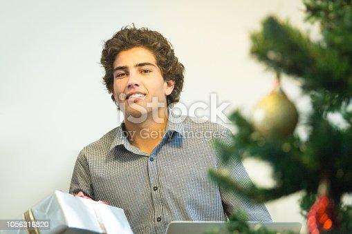 istock Teenager boy with Christmas gift 1056316820