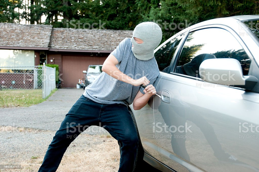 Teenager breaking into a car stock photo