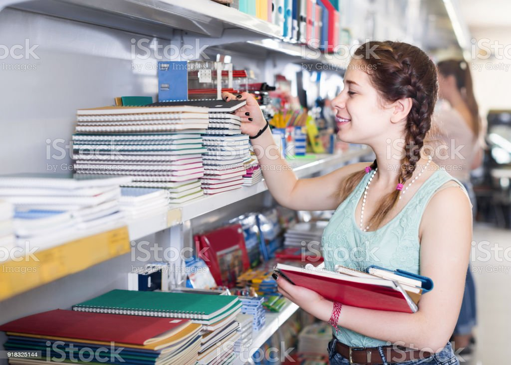 teenager buying different products in stationery shop stock photo