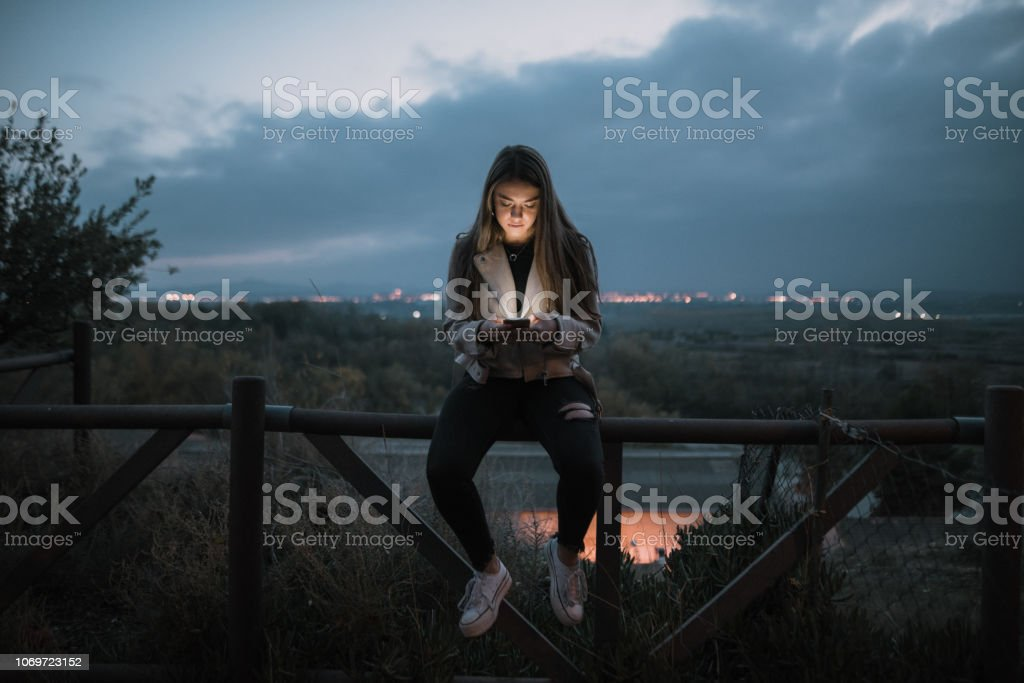 Teenager checking her smartphone - foto stock