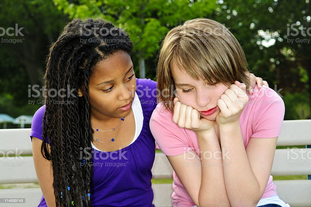 Teenager consoling her friend stock photo