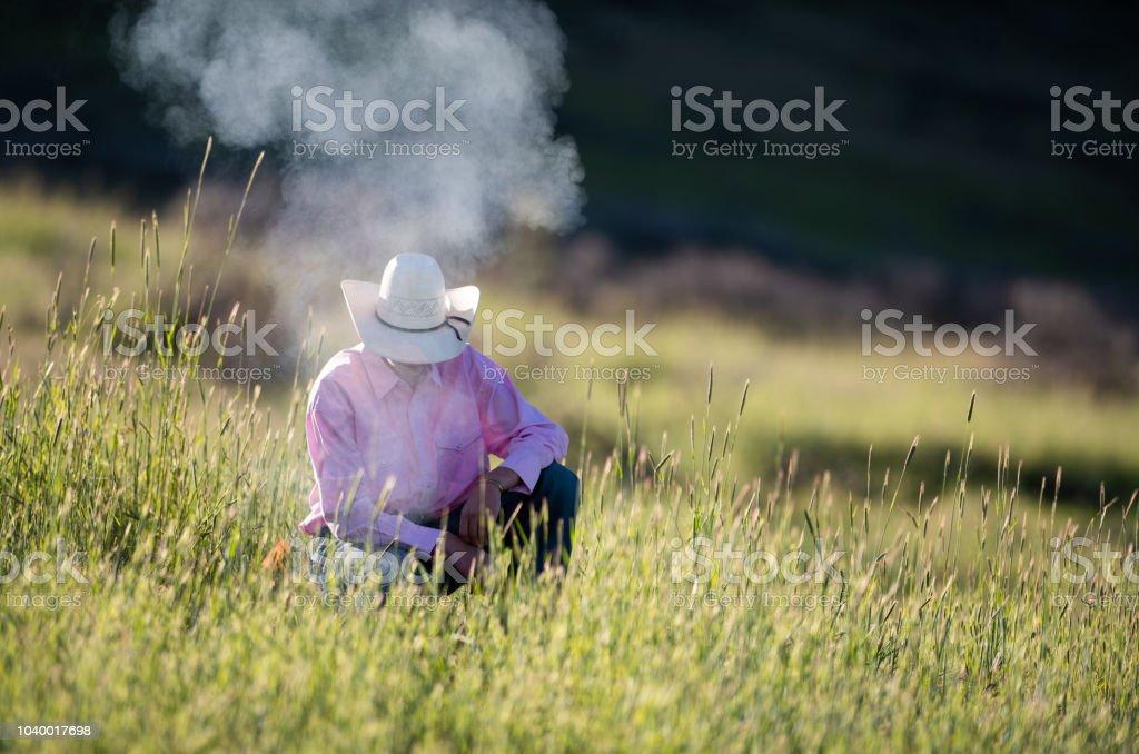Teenager cowboy preparing campfire stock photo
