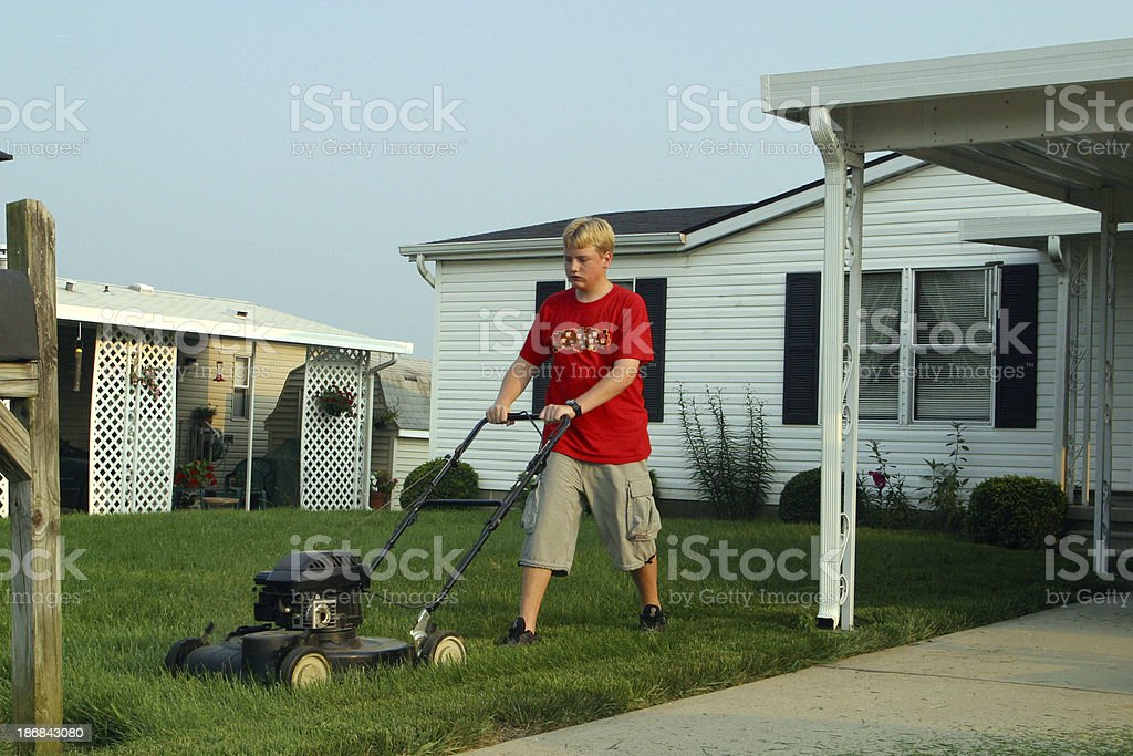 Teenager Cutting Grass royalty-free stock photo