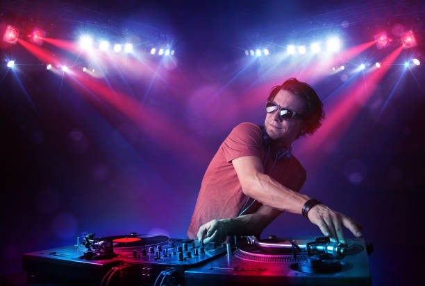 Teenager dj mixing records in front of a crowd on stage stock photo