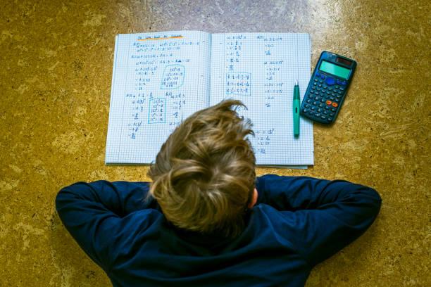 Teenager macht Hausaufgaben auf dem Boden liegen – Foto