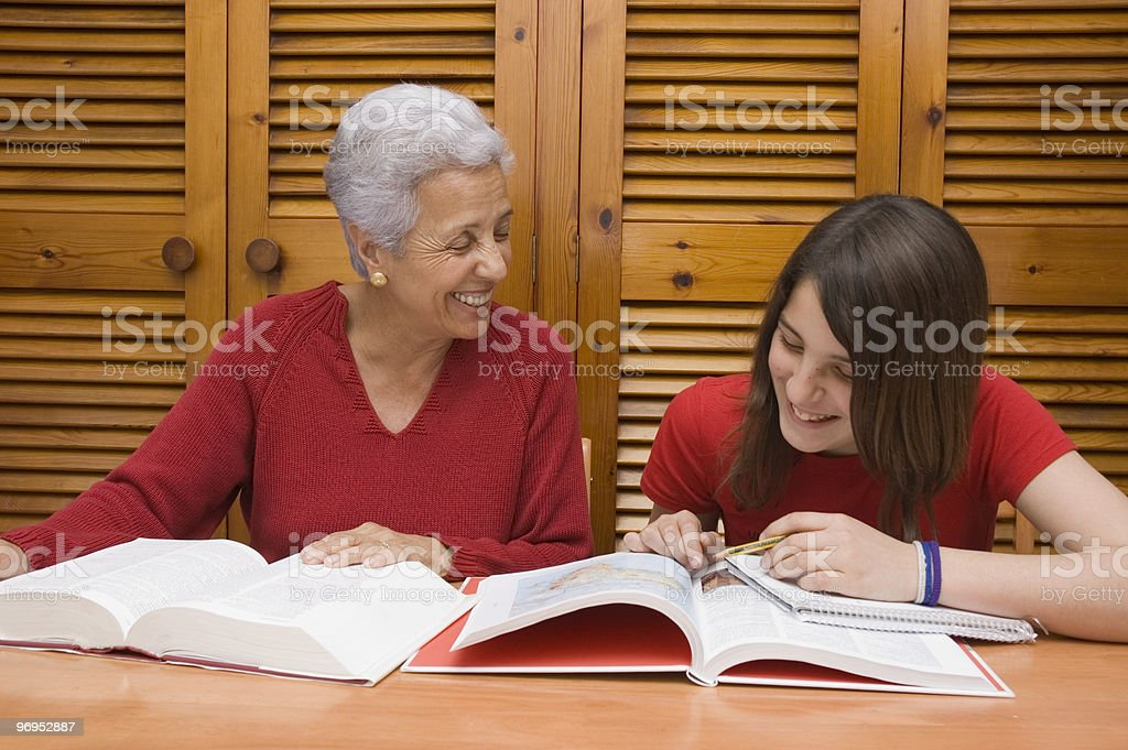 Teenager doing homework with  grandmother royalty-free stock photo