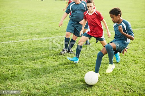 Lifestyle children training and playing soccer. A teenager dribbles his opponents during a soccer game.