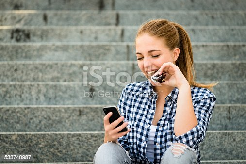Teenager - young woman eating chocolate in street and looking in phone