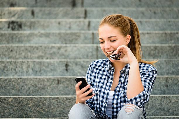 Teenager Essen chcolate blickt in Telefon – Foto