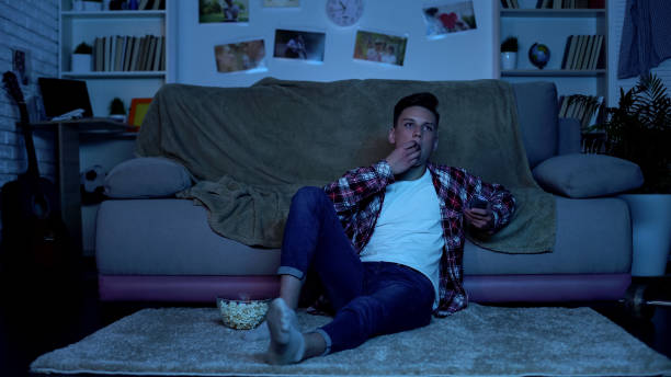 teenager eating popcorn and switching channels on tv, wasting time, boredom - divano procrastinazione foto e immagini stock