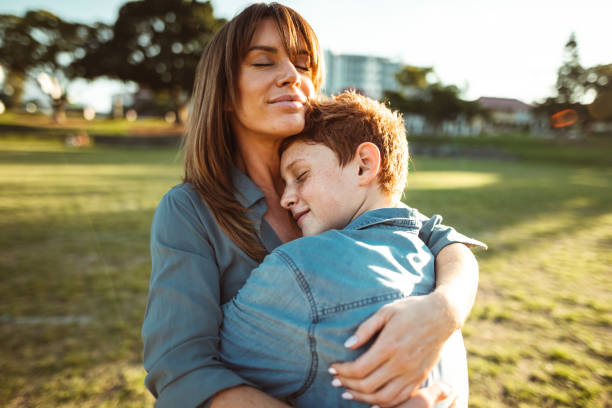teenager embraced with mom consoling her son stock photo