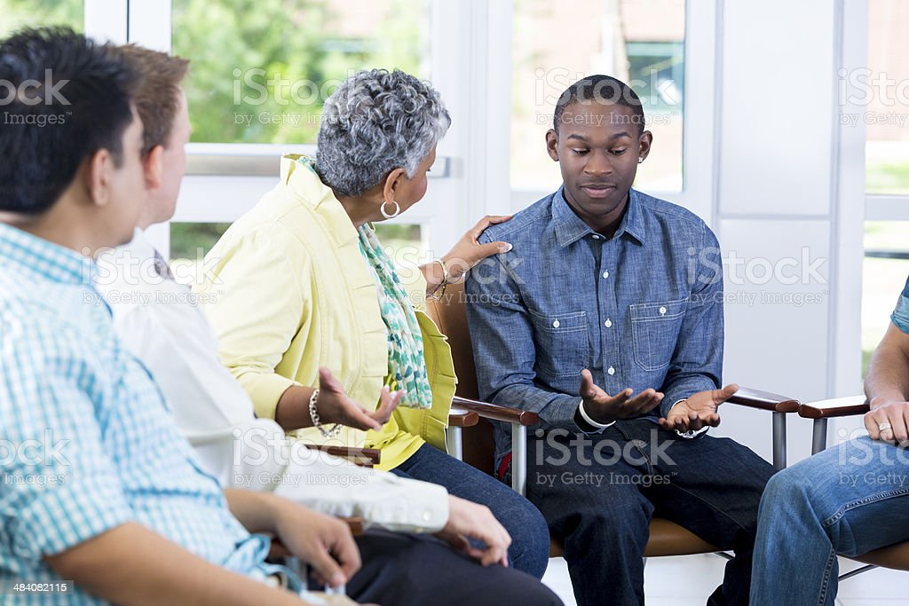 Teenager explaining problems in group setting stock photo