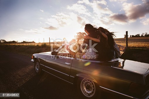 Group of teenager friends celebrating their road trip on a vintage convertible car hugging joyously with sunset sun flare
