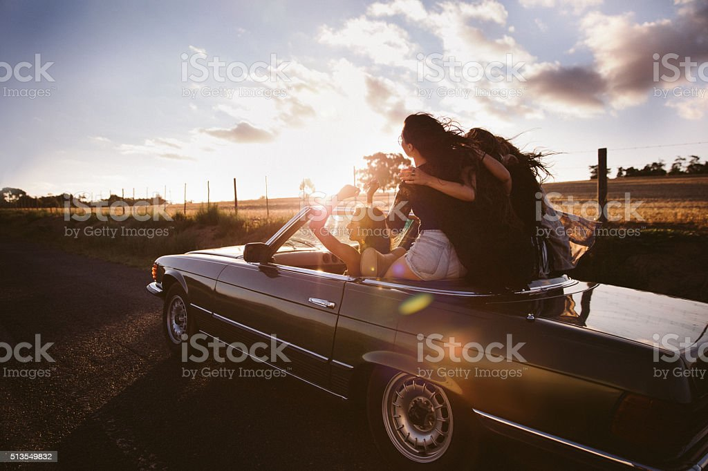 Teenager friends embracing joyfully on their road trip at sunset stock photo