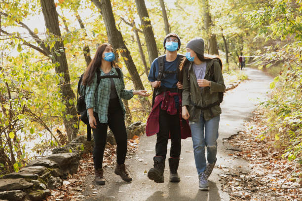 Teenager friends hiking outside in nature wearing mask