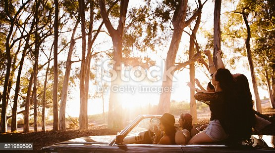Side view of a group of teenager friends on a convertible car raising arms to celebrate a summer road trip with summer sunset sun flare