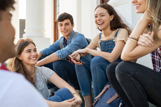 teenager-freunde sitzen zusammen und lachen - jugendalter stock-fotos und bilder