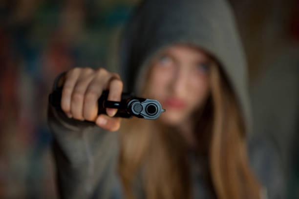 Teenager Girl Aiming a gun at the camera,, blurred focus – Foto
