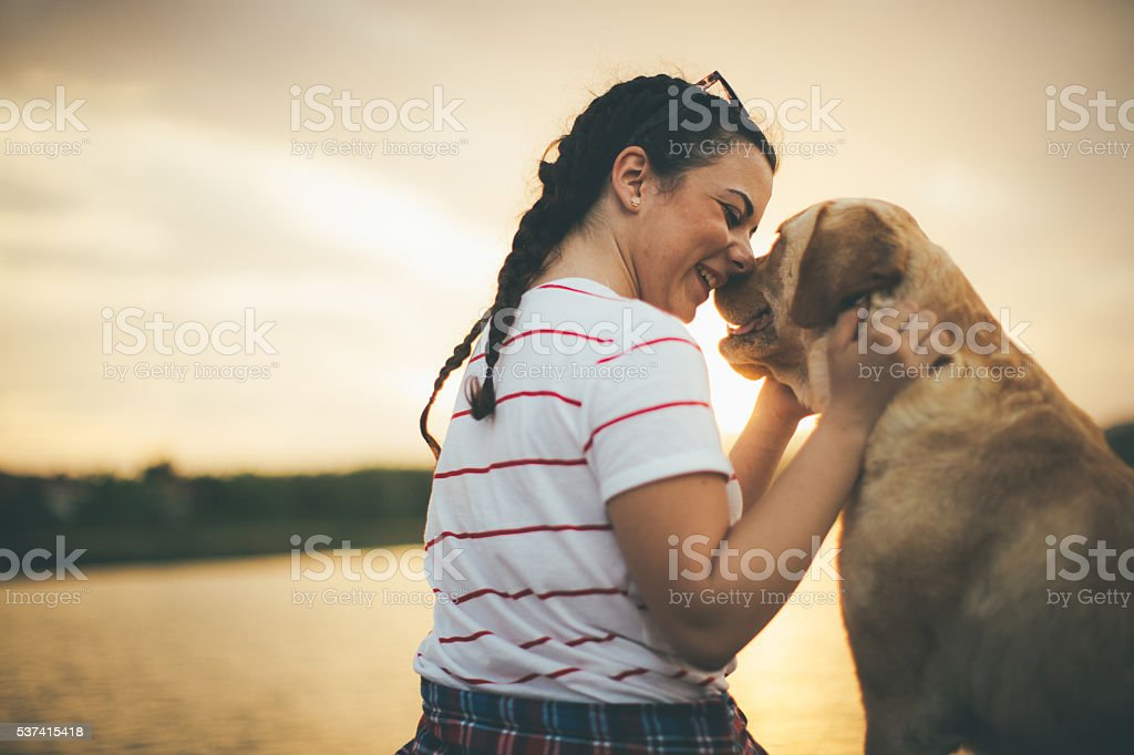 Teenager girl and her dog enjoying in golden sunset stock photo