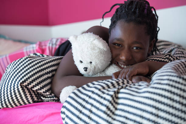 Teenager girl and teddy bear in pink cosy bedroom stock photo